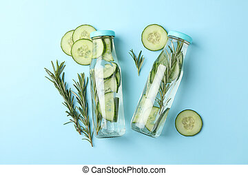 Bottles with infused cucumber water on blue background, top view