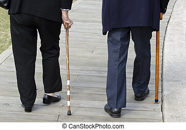 Bottom half of an elderly couple walking with a wood cane...
