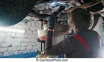 Bottom of car - Worker mechanic checks - automobile service, wide angle