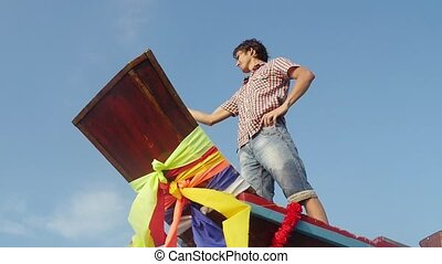 Bottom of view of young man stands on nose of a wooden boat takes selfie with mobile phone on the blue sky on the background. slow motion.