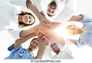 bottom view. a team of doctors at the medical center clasped...