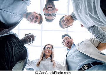 bottom view. business team standing together. the concept of...