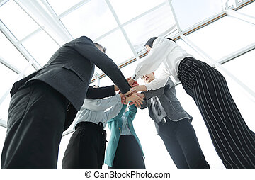 bottom view. business team with folded tower out of their hands.