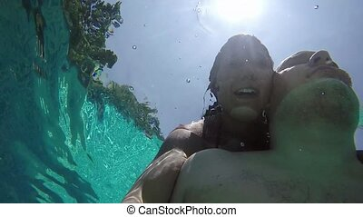 Bottom view from the water of young couple taking a selfie in the Swimming Pool against the sun and water droplets.