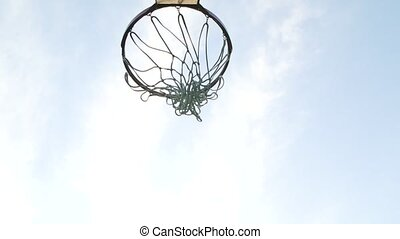 Bottom view of a basketball basket into which the ball flies. Hoop against the blue sky. Close up. Slow motion.
