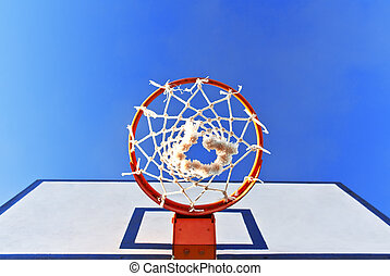 Bottom view of a basketball hoop in the street