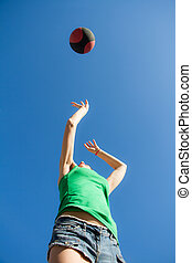 Bottom view of a girl in a jump throws a basketball over the blue sky, sports concept