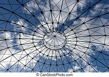 Bottom view of an iron structure with blue sky and clouds