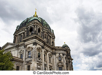 Bottom view of Berliner Dom with cloudy sky background. Majestic 1800s cathedral with an organ with 7,000 pipes, plus royal tombs & a dome for city views