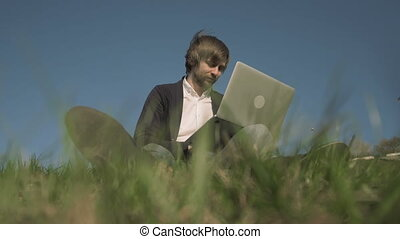 Bottom View of Handsome Hipster Using Laptop While Sitting On The Grass