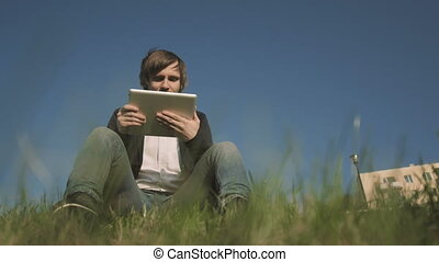 Bottom View of Handsome Hipster Using Tablet PC While Sitting On The Grass