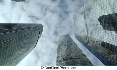 Bottom view of modern skyscrapers over cloudy sky...