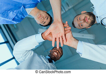 bottom view of multiracial group of doctors holding hands together in clinic