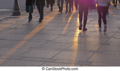 Bottom view of people legs against sunset rays on the paving...
