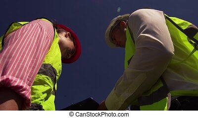 Chief Engineer And Chief Foreman Discussing - Bottom View Of...