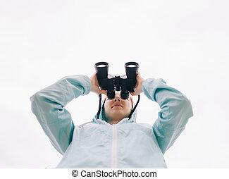 Bottom view of traveler woman watching with binoculars.