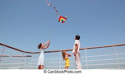 bottom view on family flying kite on deck of ship - bottom...