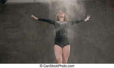 Bottom view. Slender girl blonde dancing in white powder cloud A dancer dressed in black body suit perform a modern dance in a cloud of white powder or smoke against a background of a gray wall in the studio