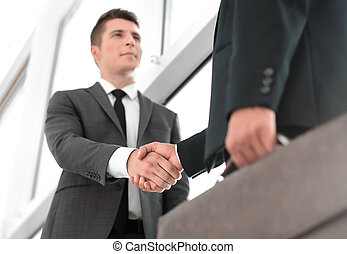 bottom view. the handshake of business people is light in the of