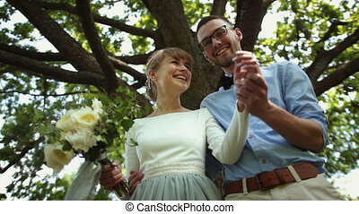Bottom view. Young beautiful newlyweds kiss against a background of green tree in the park