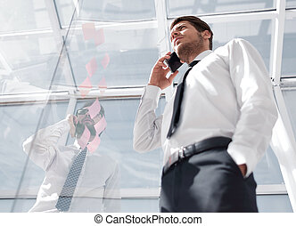 bottom view.businessman talking on mobile in the office