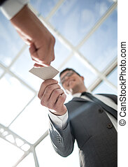bottom view.smiling businessman takes a business card.