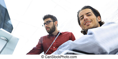 two businessman sitting at a Desk