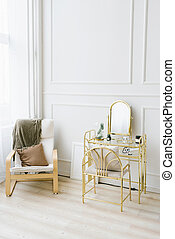 Boudoir table and chair with a blanket and pillow near the window. Interior details of bedrooms for girls and women