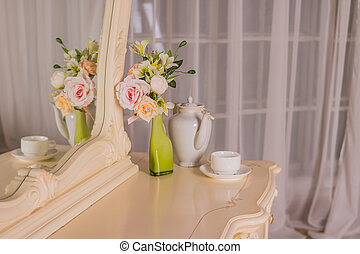 Boudoir table. Details of the interior of the bedroom for girls and make-up, hairstyles with a mirror. Good morning coffee in bed. Boudoir table, dressing table. Romantic design for bedroom.