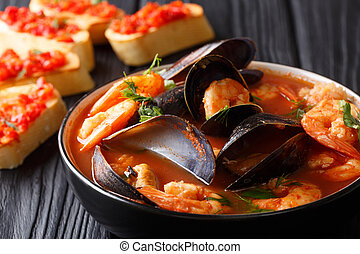 Bouillabaisse soup with seafood and fish close-up in a bowl served with toasts. horizontal