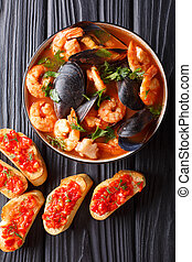Bouillabaisse soup with seafood and fish close-up in a bowl served with toasts. Vertical top view
