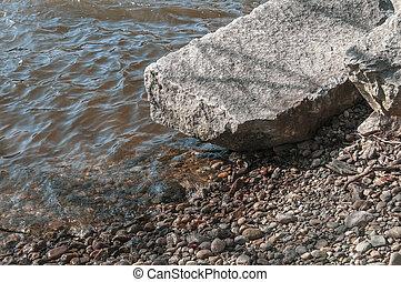 Flat boulder lying on rocky edge of Blackstone River