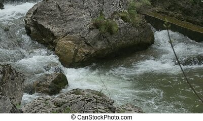 Boulder on Mountain River - Foamy water flowing around a big...