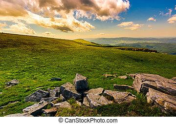 boulder on the grassy hillside at sunset - boulder on the...