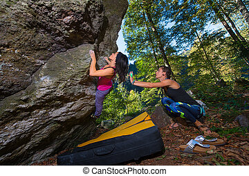 Bouldering practice. two girls with the crash pad