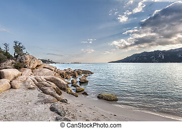 Boulders in a turquoise sea at Santa Giulia beach in Corsica...