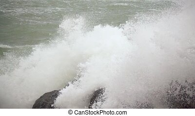 Boulders on the shore break the waves slow mo