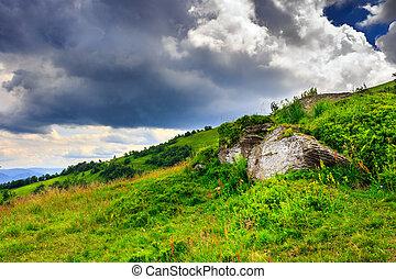 boulders under a large cloud - boulders on a mountain top...