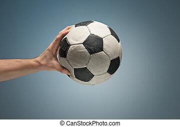 boule football, tenant mains