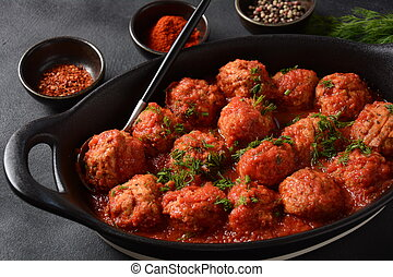 Boulettes de Poisson, Fried Fish Balls in Tomato Sauce in a black dish on a concrete table with ingredients