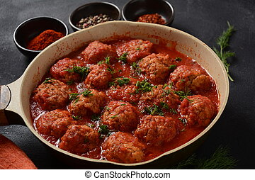 Boulettes de Poisson, Fried Fish Balls in Tomato Sauce in a white dish on a concrete table with ingredients