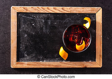 Boulevardier cocktail and orange zest on black slate ...