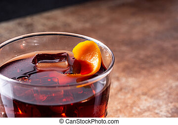 Boulevardier cocktail and orange zest on rusty background