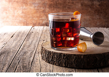 Boulevardier cocktail and orange zest on rusty background.