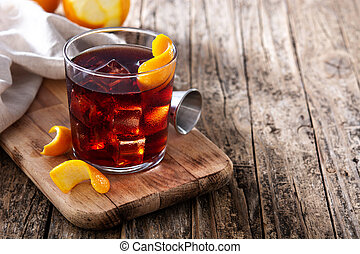 Boulevardier cocktail and orange zest on wooden table. Copy ...