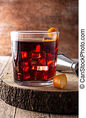 Boulevardier cocktail and orange zest on wooden table
