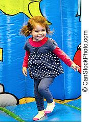 Bouncy castle - Happy little girl jumps in a bouncy castle.