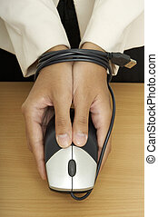 A woman holds a mouse over a desk. The mouse cable is tied around her wrists.