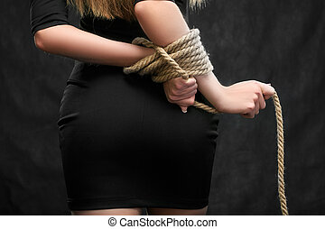 female hands tied behind his back with a rope
