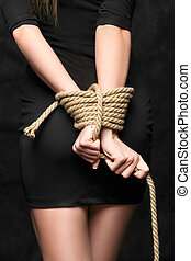 bound hands - female hands tied behind his back with a rope